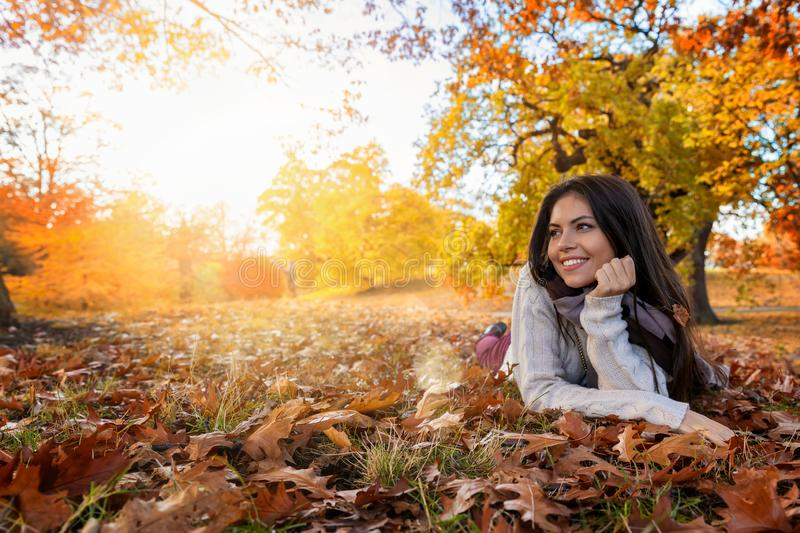 Woman enjoys the sunshine in the park in autumn. Autumn concept with copy space: attractive woman enjoys the sunshine in the park with colorful leaves in autumn stock photo