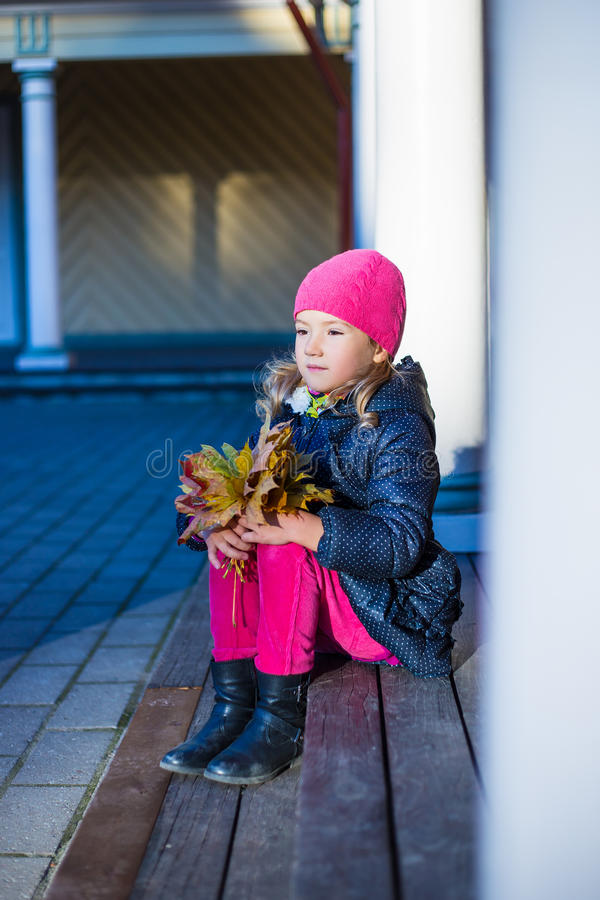 Autumn concept - daydreaming little girl with yellow leaves sitt stock images