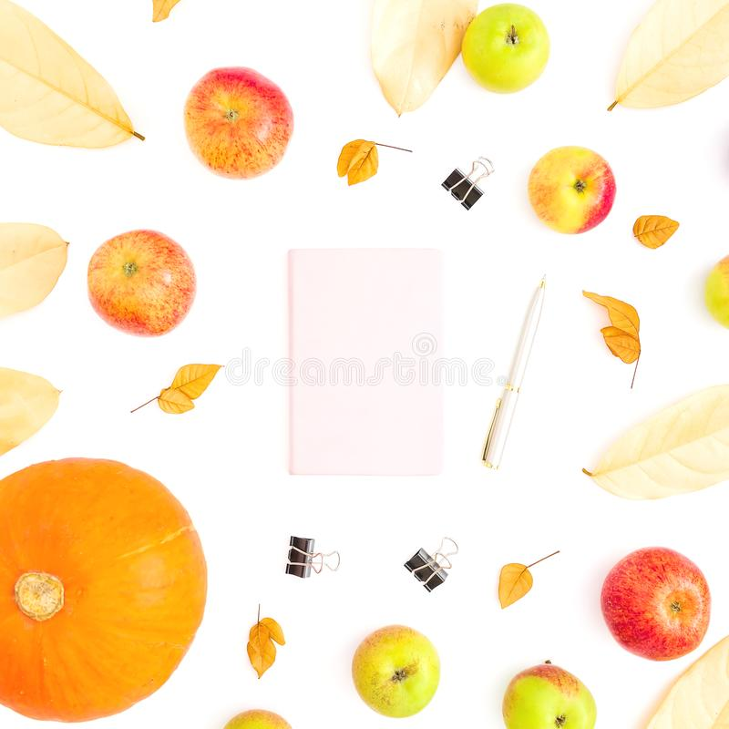 Autumn concept of fall leaves, apple fruit and pumpkin with notebook, pen and clips on white background. Thanksgiving day. Flat la royalty free stock images