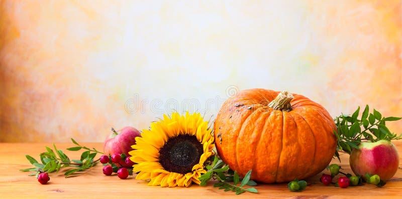 Autumn concept. With flowers,pumpkin and seasonal fruits stock photos