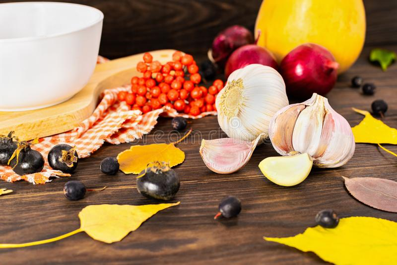 Autumn concept with garlic and grown pumpkins, red onions, rowan, rosehip and autumn leaves on wooden background. Top view stock photo