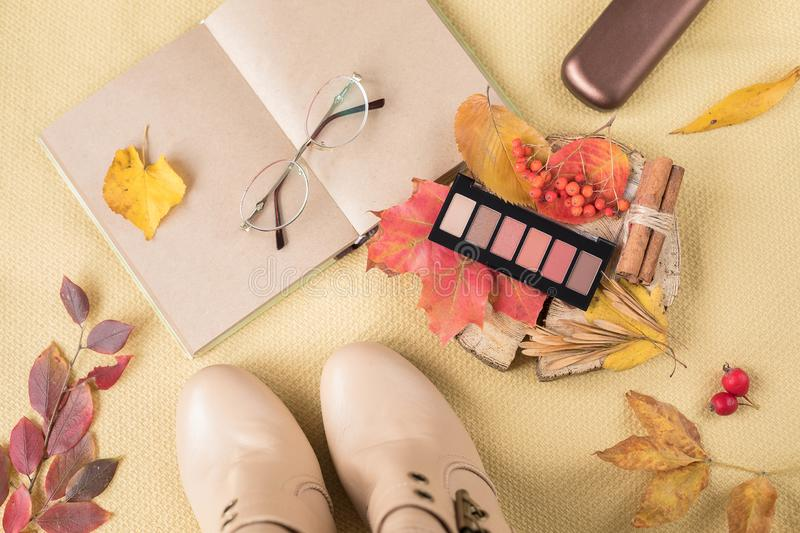 Autumn concept: a palette of autumn paints in a stick of shadows shade nude for makeup, beige women `s boots, a notebook for royalty free stock photo