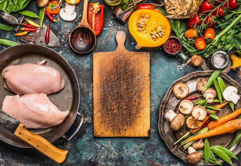Autumn cooking with organic harvest vegetables, pumpkin and chicken on rustic kitchen table background with empty cutting board. Top view, frame royalty free stock photography