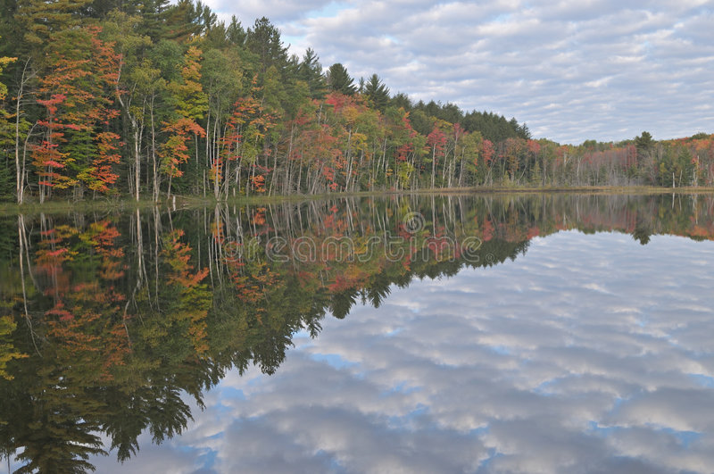 Autumn Council Lake. With reflections of colorful foliage and cloud filled sky, Michigan's Upper Peninsula, USA royalty free stock images