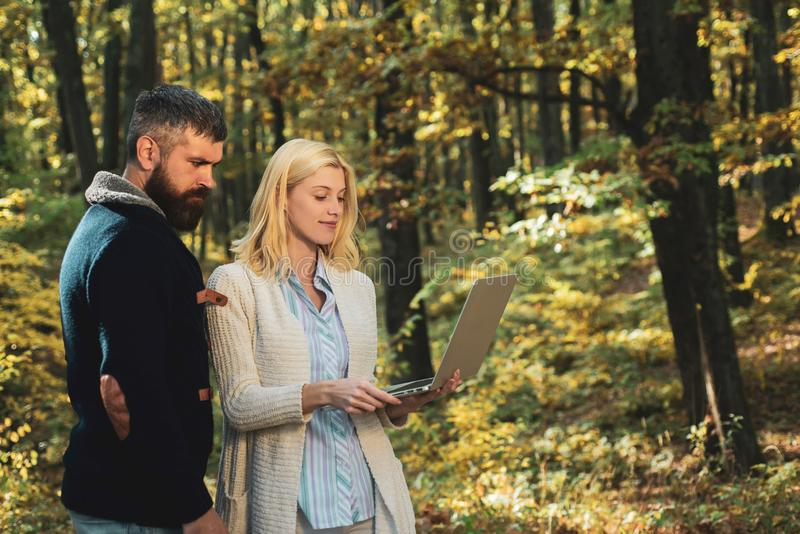 Autumn couple. Business couple - browsing mobile Internet on a notebook outdoors. Business outdoor in autumn park. royalty free stock images