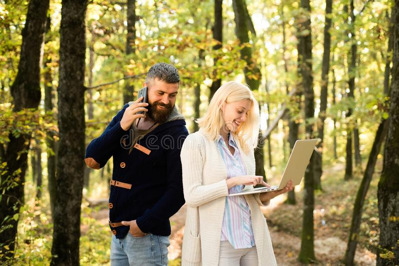 Autumn couple. Working in nature. Business outdoor. Business couple - man browsing Internet on a mobile phone , woman. Autumn couple. Working in nature. Business stock photography