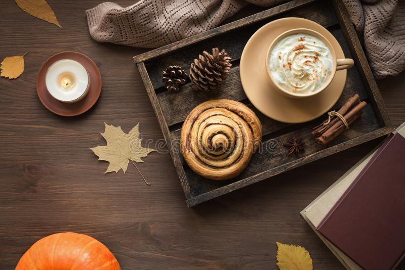Autumn cozy flat lay. Cozy home and autumn hygge concept. Seasonal autumnal composition with soft plaid, coffee latte, fresh cinnamon bun, candle, pumpkin on stock photo