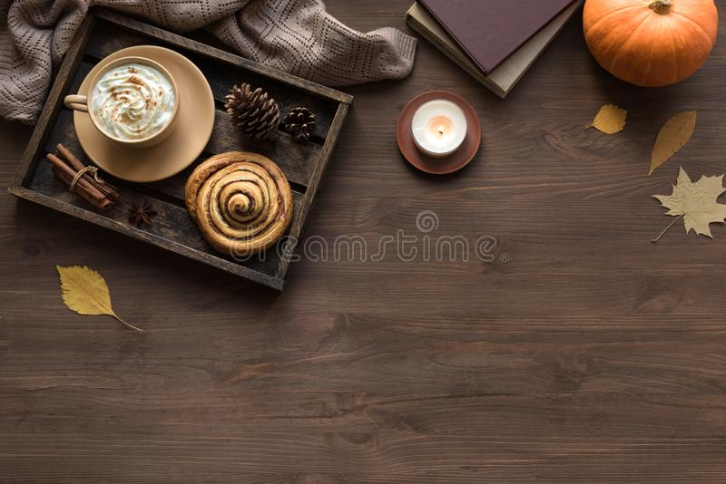 Autumn cozy flat lay. Cozy home and autumn hygge concept. Seasonal autumnal composition with soft plaid, coffee latte, fresh cinnamon bun, candle, pumpkin on royalty free stock photo