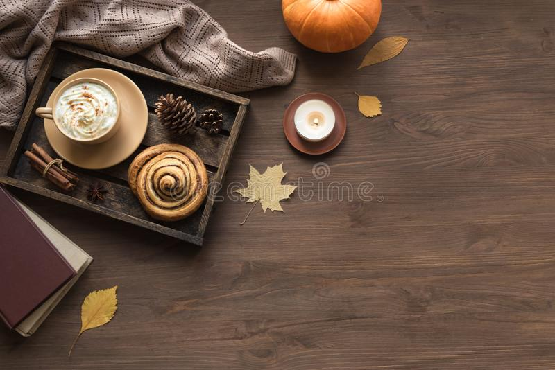 Autumn cozy flat lay. Cozy home and autumn hygge concept. Seasonal autumnal composition with soft plaid, coffee latte, fresh cinnamon bun, candle, pumpkin on stock images
