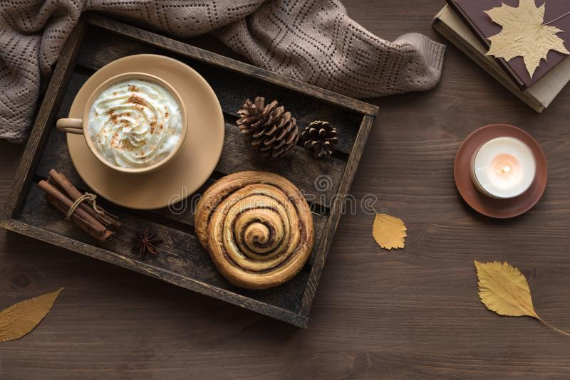 Autumn cozy flat lay. Cozy home and autumn hygge concept. Seasonal autumnal composition with soft plaid, coffee latte, fresh pastry cinnamon bun, candle on royalty free stock images