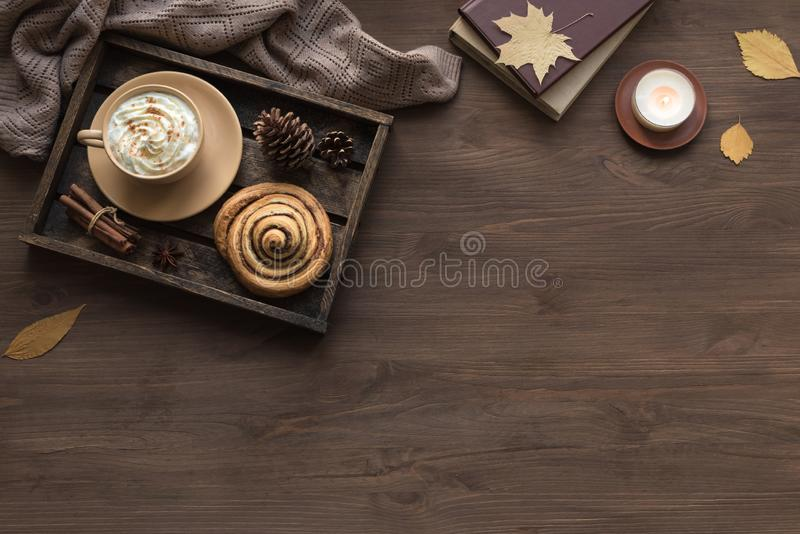 Autumn cozy flat lay. Cozy home and autumn hygge concept. Seasonal autumnal composition with soft plaid, coffee latte, fresh pastry cinnamon bun, candle on stock photo