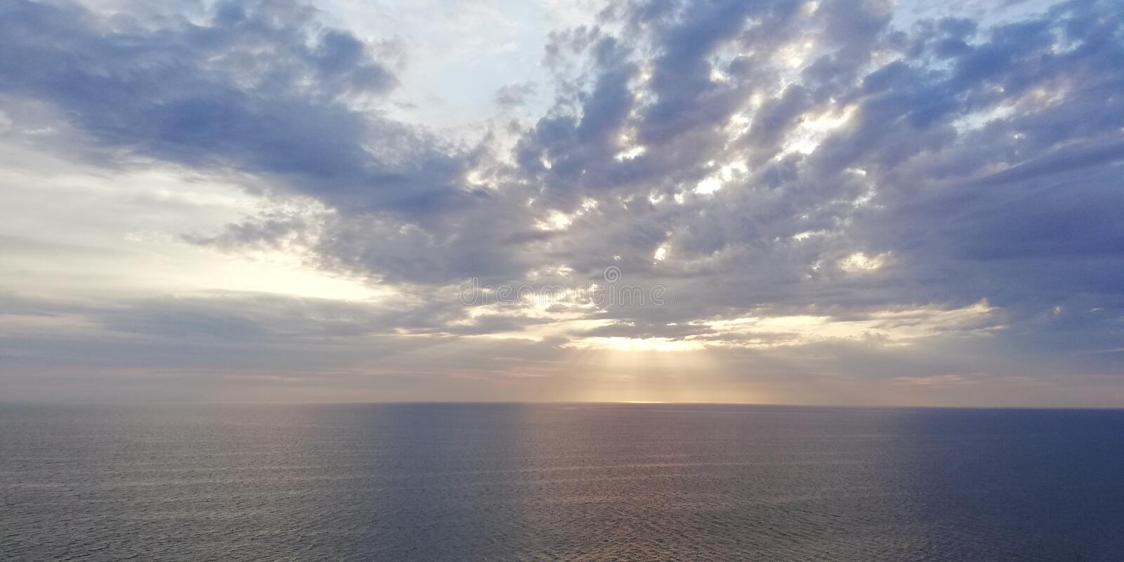 Autumn sunset seascape. Clouds, sea and setting sun. Background. The autumn dark sea is illuminated by the setting sun, peeking through dense blue-gray clouds royalty free stock photo