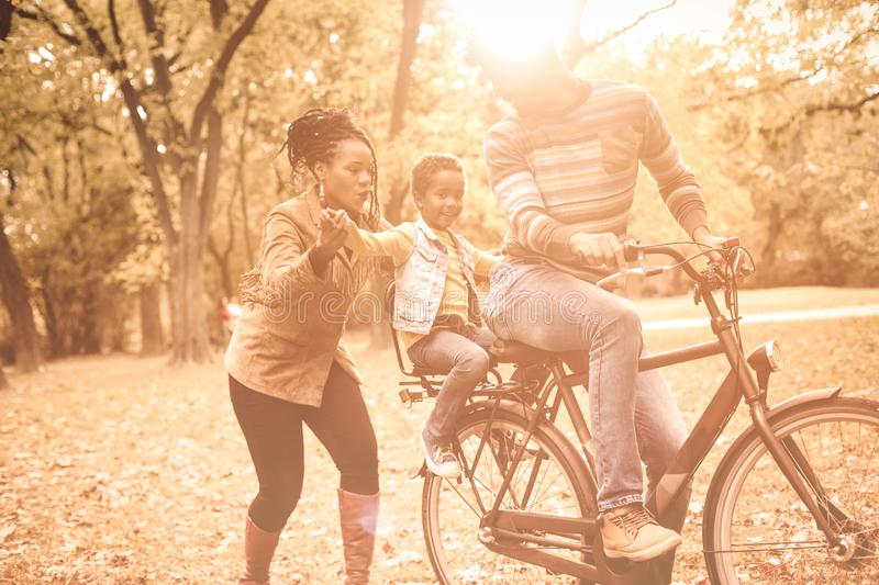 Autumn day with parents. Smiling father and mother playing with daughter little girl sitting with father on bike stock image