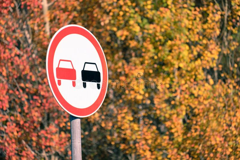 In the autumn day under the bright sun and the road sign overtaking is prohibited on the background of autumn leaves. On the tree stock photography