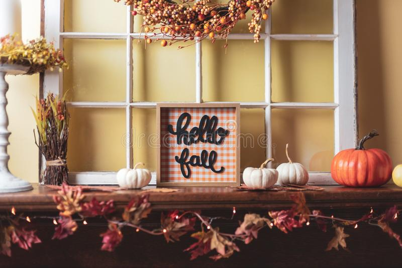 Fall decorations on the fireplace mantel. Autumn decor - Hello Fall on the fireplace mantel stock photo