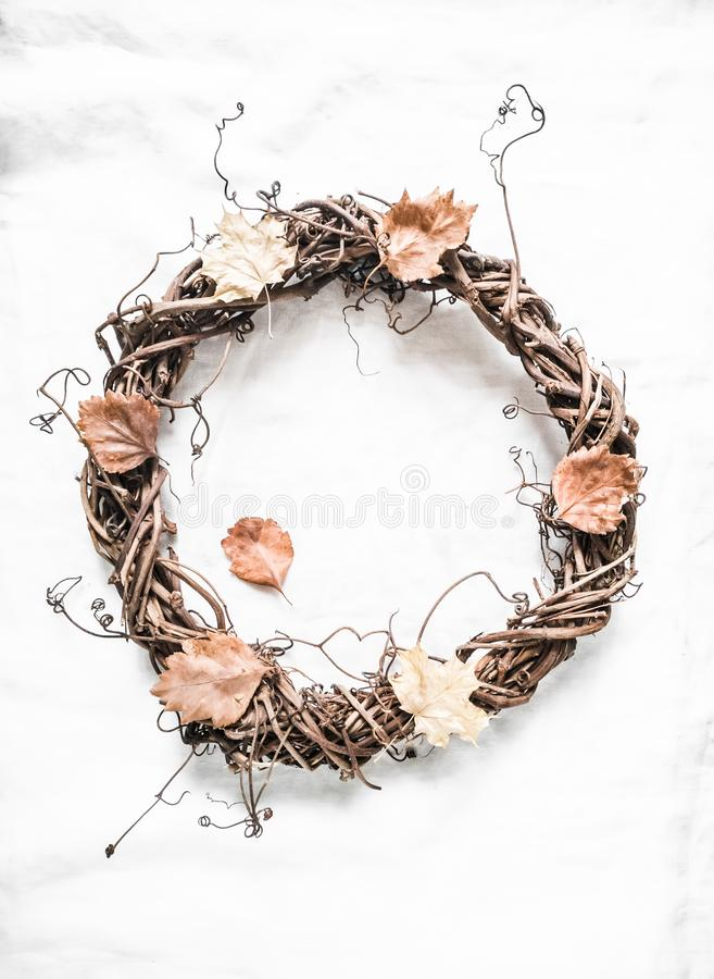 Autumn decorative vine wreath on a light background, top view. Homemade creativity concept royalty free stock photo