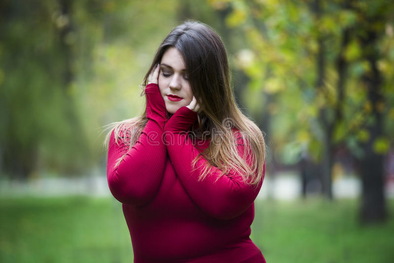 Autumn depression, young beautiful caucasian plus size model in red pullover outdoors, xxl woman on nature, fall atmosphere royalty free stock images