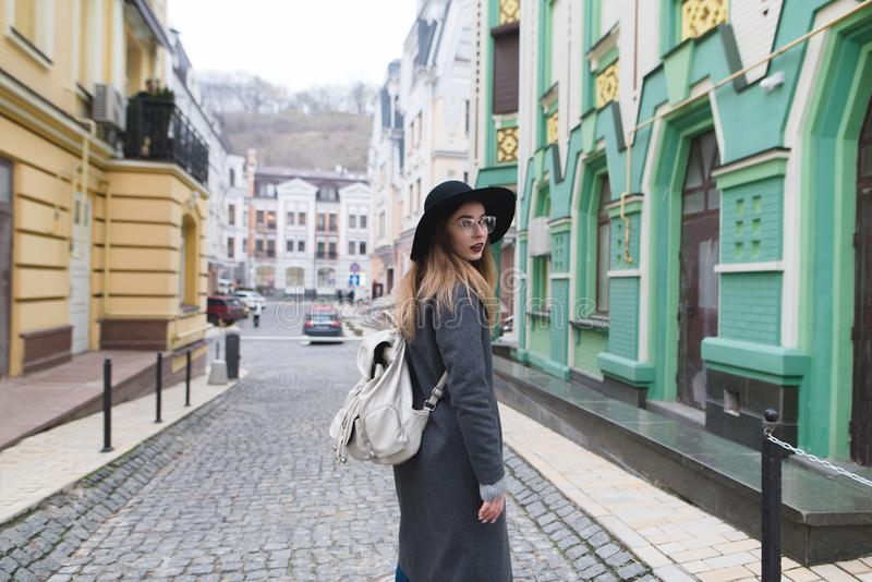 In the autumn dressed woman walks along the streets of the old town. Stylish tourist girl walking in a beautiful town. royalty free stock image