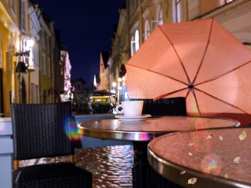 Autumn evening in city street cafe cup of coffee on table rainy night pink umbrella Old Town Of Tallinn. Tallinn  panorama old town   Estonia capital city royalty free stock photography