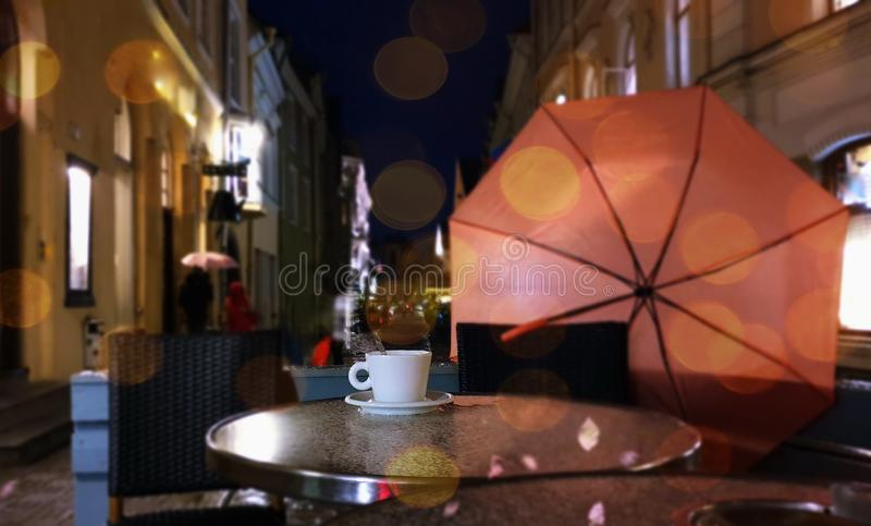Autumn evening in city street cafe cup of coffee on table rainy night pink umbrella Old Town Of Tallinn. Tallinn  panorama old town   Estonia capital city royalty free stock photos