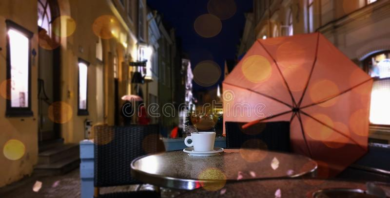 Autumn evening in city street cafe cup of coffee on table rainy night pink umbrella Old Town Of Tallinn. Tallinn  panorama old town   Estonia capital city stock images