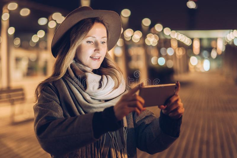 Autumn evening. Young woman in hat and scarf stands on city street, uses smartphone. Hipster girl uses digital gadget. royalty free stock images