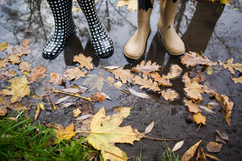 Girl wearing rain boots standing in a puddle on warm summer day stock photo