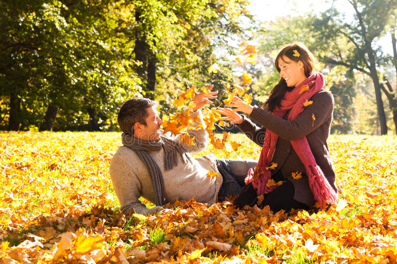 Autumn fall couple. Playing with leaves royalty free stock photo