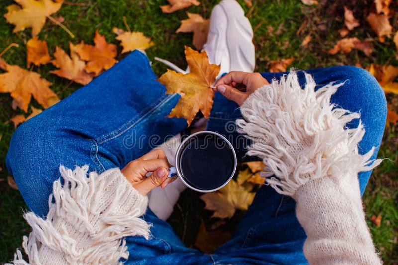 Autumn concept. Beautiful woman wearing white sweater with coffee mug sitting against fall nature background. royalty free stock photo
