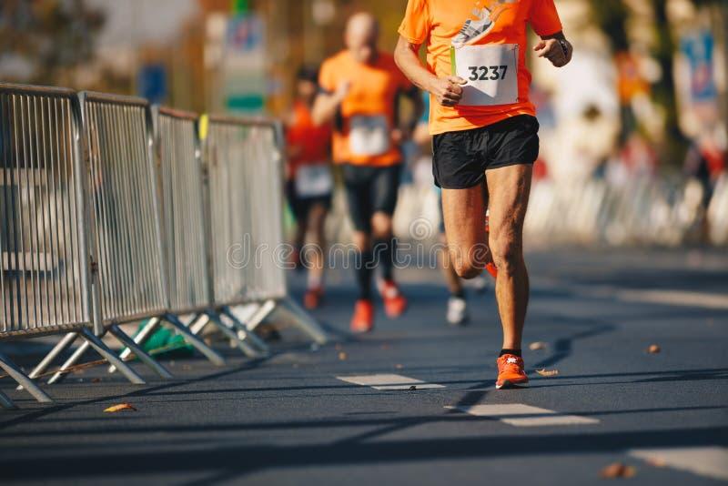 Autumn fall marathon race in city. Marathon running race, people feet on autumn road. Runners run urban marathon in the downtown royalty free stock photos
