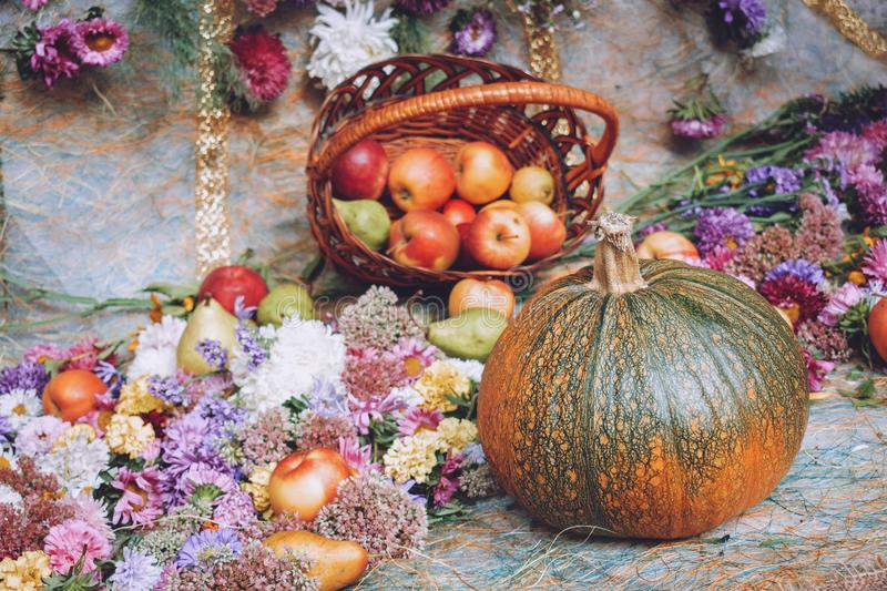 Autumn fall seasonal decorations with pumpkins, fresh fruits in basket, berries and flowers. Autumn harvest, farm market, sale stock image