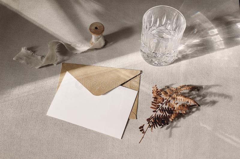 Autumn, fall stationery mockup scene. Blank greeting card, invitation, craft paper envelope, dry fern leaf and sparkling. Glass of water on grey table linen stock photography