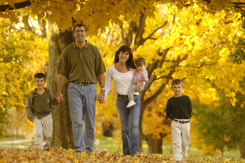 Autumn family. A family of five walks through fallen leaves on a warm fall afternoon