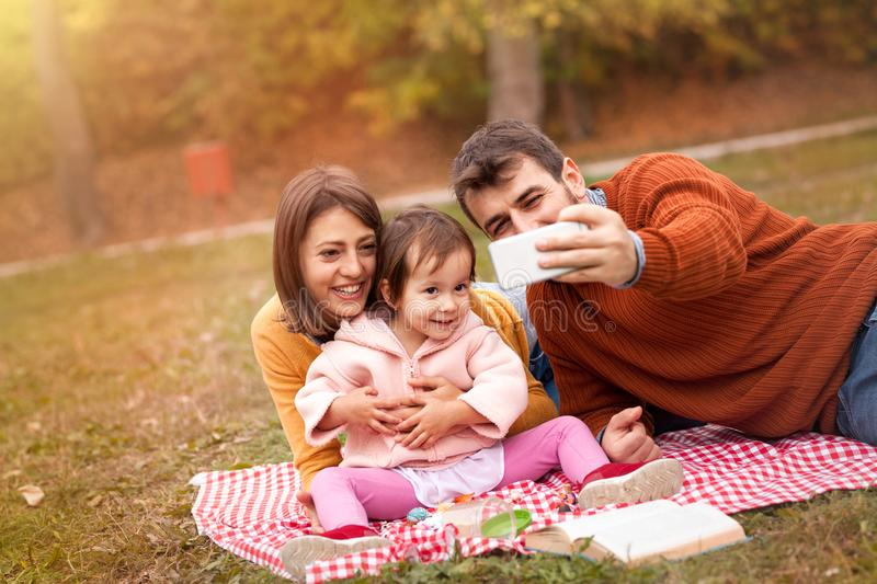 Autumn family picnic on grass smiling and making selfie. Autumn family picnic on grass in park under gentle shade of trees. Mother, father and child sitting on stock image