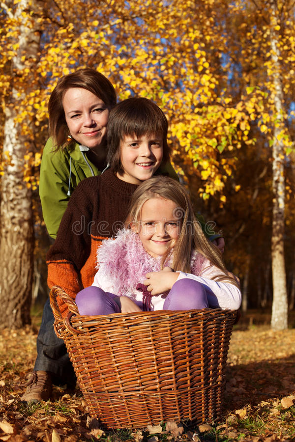 Autumn family portrait. Preparing to gather the leaves in the garden stock photography