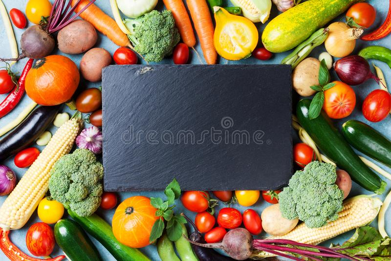 Autumn farm vegetables, root crops and slate cutting board top view with copy space for menu or recipe. Healthy food background. stock image