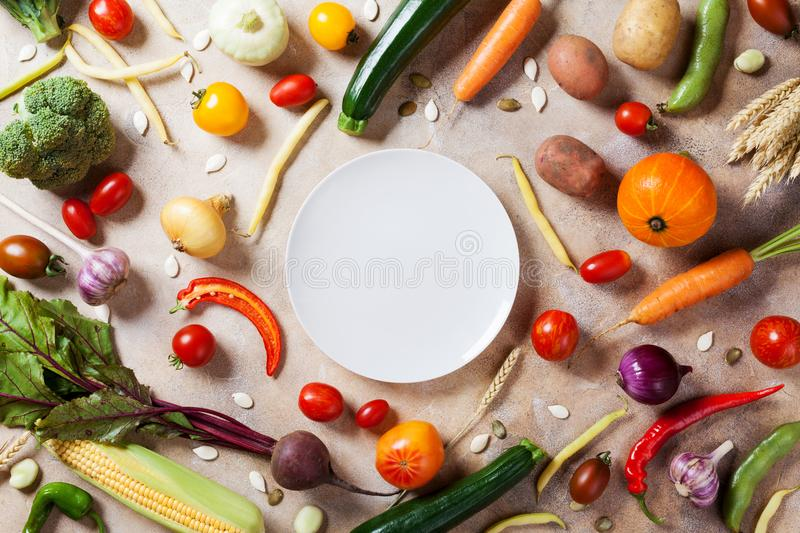 Autumn farm vegetables, root crops and white plate top view with copy space for menu or recipe. Healthy food on kitchen table. Autumn farm vegetables, root stock photography