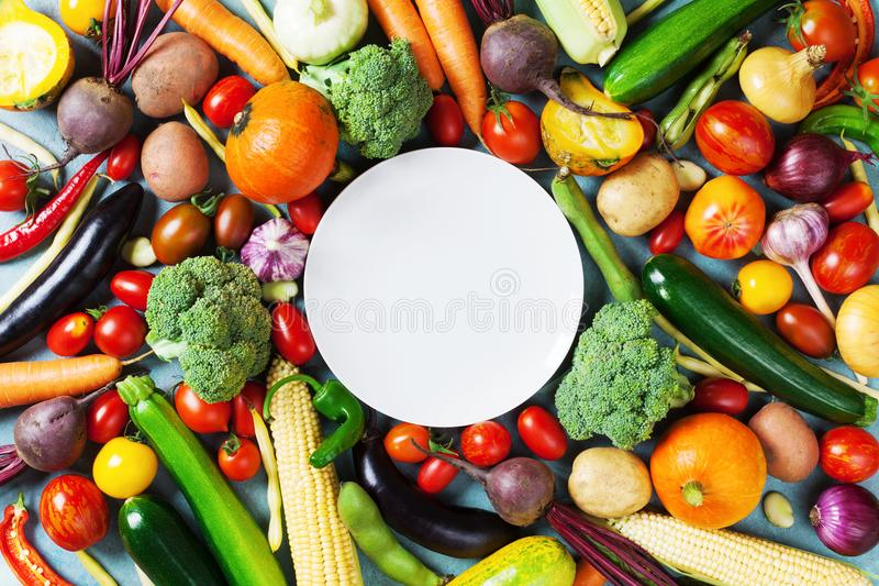 Autumn farm vegetables, root crops and white plate top view with copy space for menu or recipe. Healthy and organic food. Autumn farm vegetables, root crops and royalty free stock photos