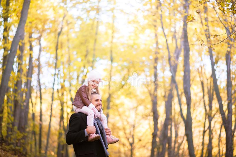 Autumn fashion for children and the whole family. A small daughter sits on the shoulders of the father in the neck against the bac royalty free stock images