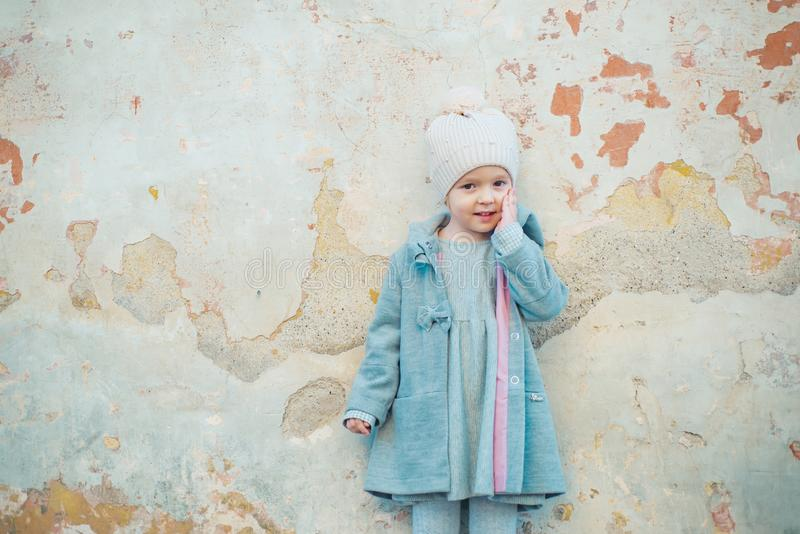 Autumn fashion. childrens day. little girl in vintage coat on grunge background. Beauty. retro style. copy space. small stock photo