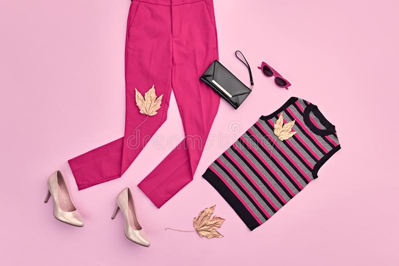 Autumn Fashion Clothes Flat lay, Leaf. Fall Outfit. Autumn Arrives. Fashion Lady Clothes fall Outfit. Trendy top, pink trousers. Stylish Handbag, Glamour heels royalty free stock photo