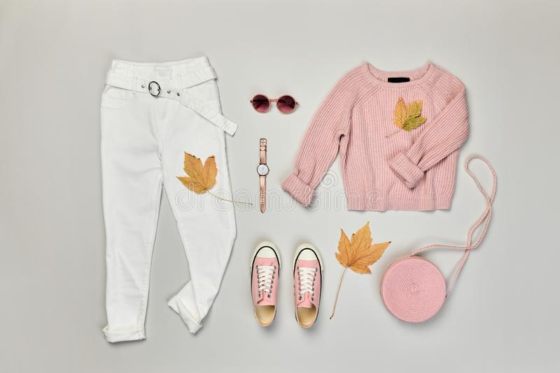 Autumn Fashion Clothes Outfit Flat lay. Maple Leaf. Fall fashion Flat lay. Trendy pink jumper, Stylish trousers, hipster sneakers, autumn Maple Leaf. Creative stock images