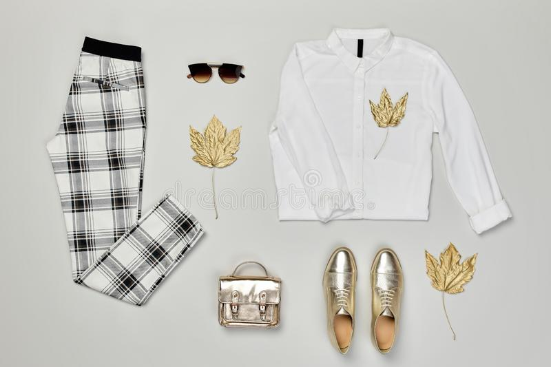 Autumn Fashion Clothes Outfit Flat lay. Maple Leaf. Fall fashion Flat lay. Trendy shirt, Stylish trousers, gold loafers shoes, glamour handbag, autumn Maple Leaf stock photo