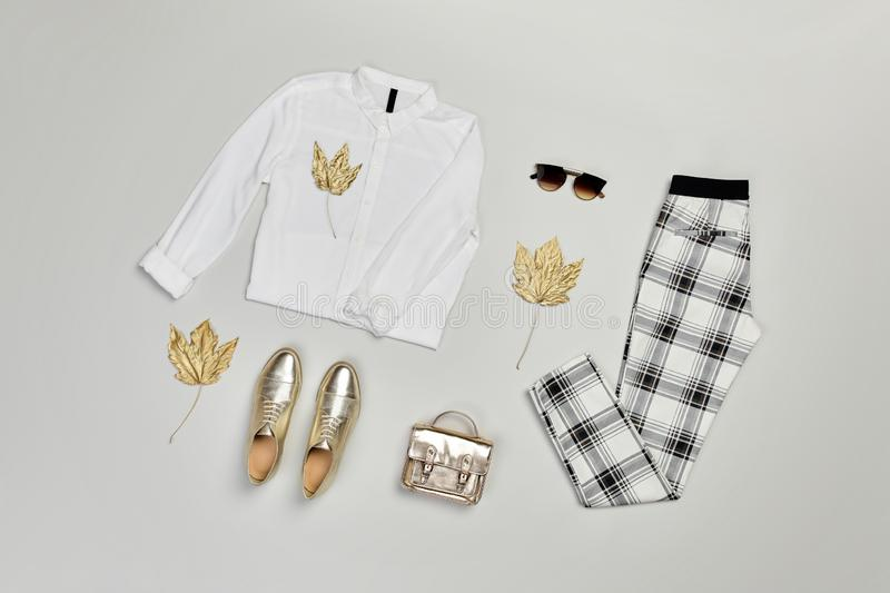 Autumn Fashion Clothes Outfit Flat lay. Maple Leaf. Fall fashion Flat lay. Trendy shirt, Stylish trousers, gold loafers shoes, glamour handbag, autumn maple leaf stock image