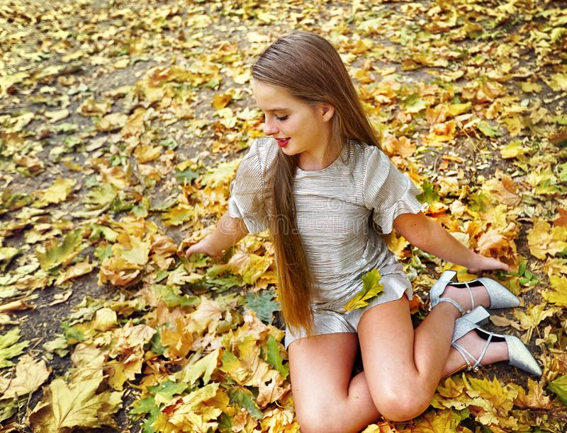 Autumn fashion dress child girl sitting fall leaves park outdoor. stock photos