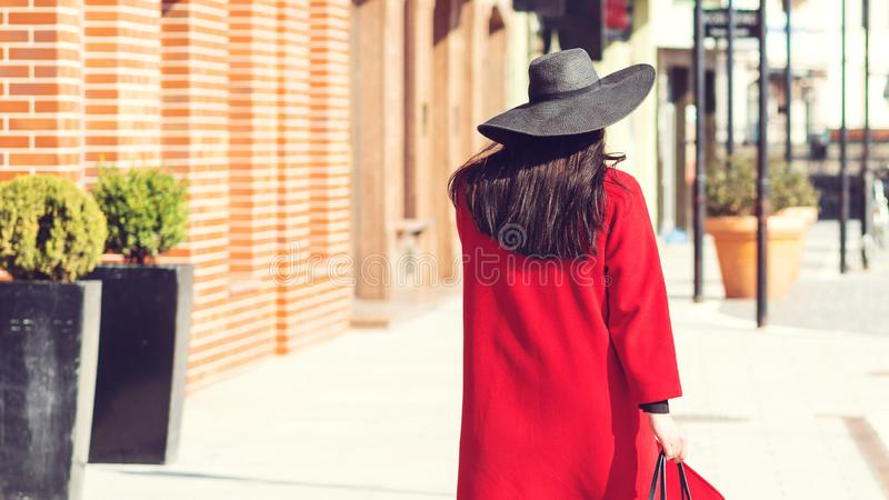 Autumn fashion. Elegant woman in red coat and stylish black hat, with trendy bag walking in city. Shopping day, great sales. royalty free stock photos