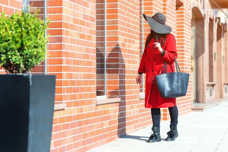 Autumn fashion. Elegant woman in red coat and stylish black hat, with trendy bag walking in city. Shopping day, great sales. royalty free stock photography