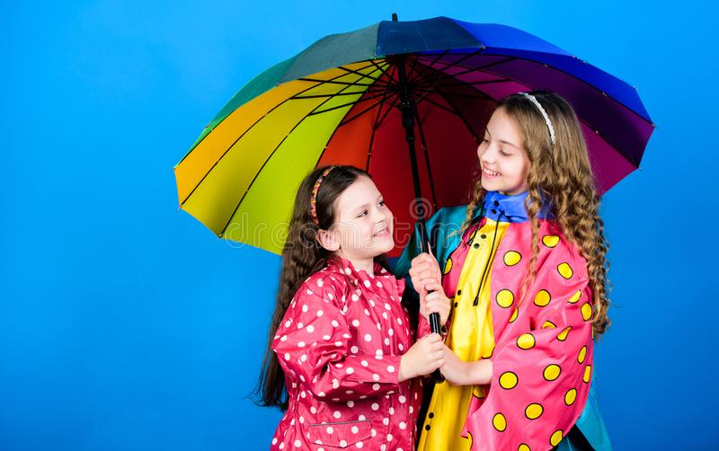 Autumn fashion. family bonds. Little girls in raincoat. rain protection. Rainbow. cheerful hipster children, sisterhood. Happy little girls with colorful stock image