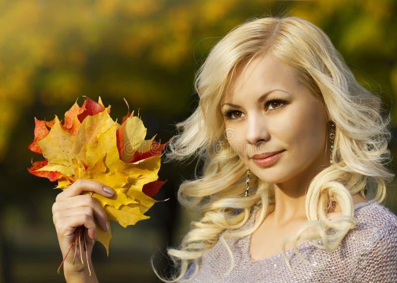 Autumn Fashion Girl. Blond härlig ung kvinna med gula lönnlöv i hand. Utanför. royaltyfri fotografi