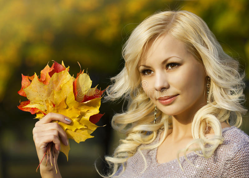 Autumn Fashion Girl. Blonde beautiful young woman with yellow maple leaves in hand. Outside. royalty free stock photography